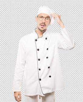 Zaniepokojony młody szef kuchni robi gest zmieszania