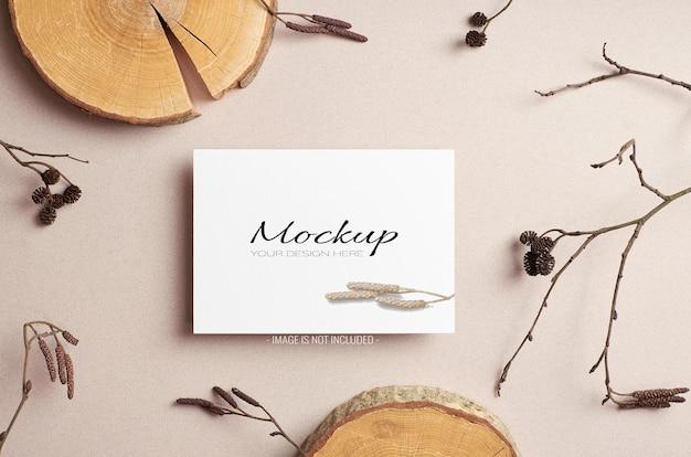 Zaproszenie lub kartka okolicznościowa makieta z suchymi gałązkami drzew i wyciętymi dekoracjami z bali