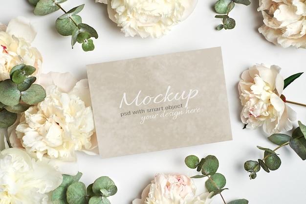 Zaproszenie lub kartkę z życzeniami stacjonarna makieta z białymi kwiatami piwonii i gałązkami eukaliptusa
