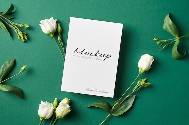 Zaproszenie lub makieta z życzeniami z białymi kwiatami eustoma na zielono