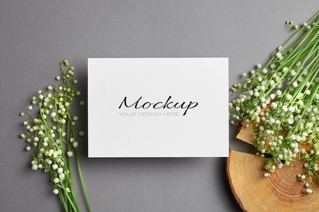 Zaproszenie lub makieta z życzeniami z bukietem kwiatów konwalii na wyciętym dzienniku