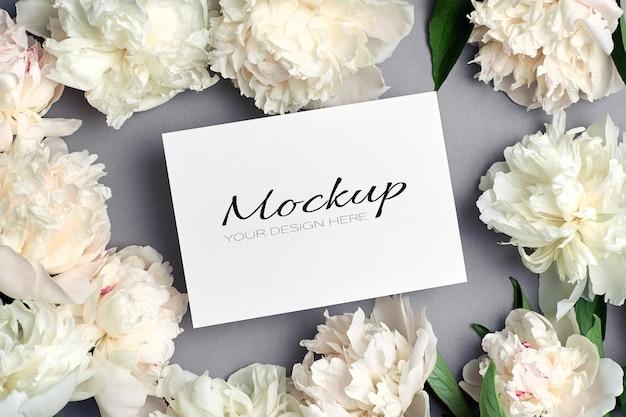 Zaproszenie na ślub lub makieta z życzeniami z białymi kwiatami piwonii na szaro