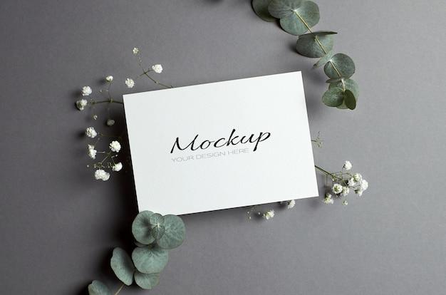 Zaproszenie na ślub lub makieta z życzeniami z kopertą i gałązkami eukaliptusa i hipsofili