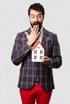 Zaskoczony dobrze ubrany mężczyzna trzyma mały dom