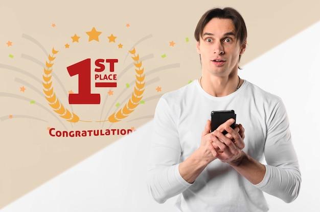 Zaskoczony mężczyzna trzyma smartphone