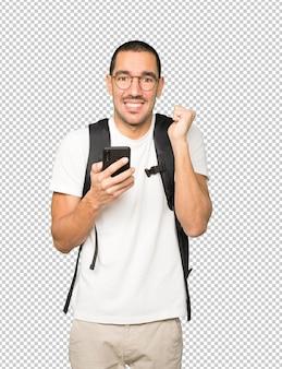 Zaskoczony student wskazując i używając swojego telefonu komórkowego