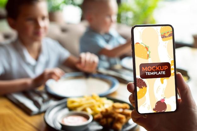 Zbliżenie dłoni trzymającej smartfon przy stole