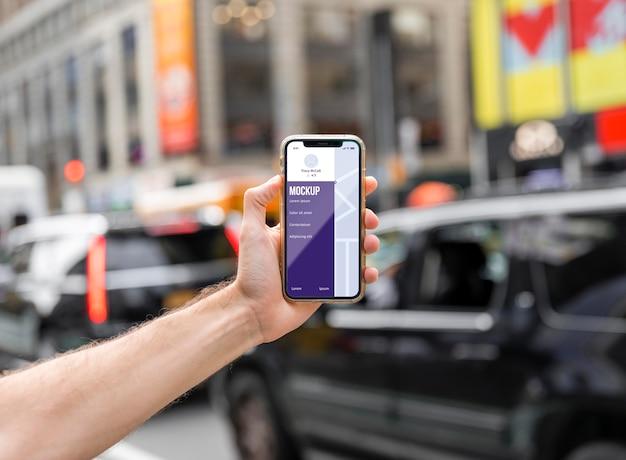 Zbliżenie dłoni trzymającej smartfon w mieście
