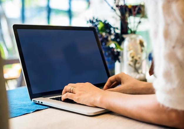 Zbliżenie kobieta używa laptop