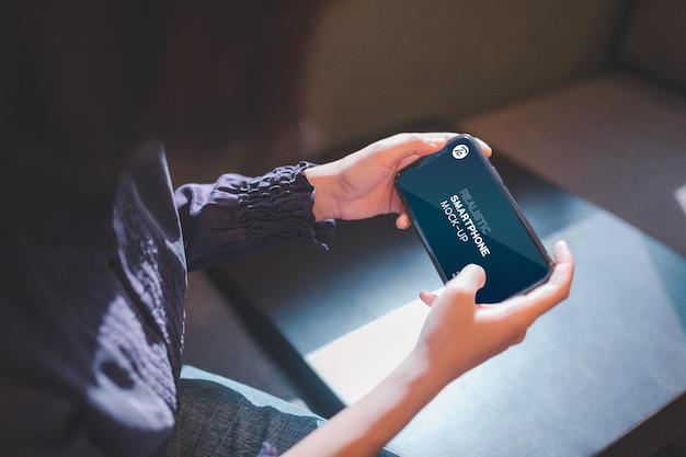 Zbliżenie kobiety za pomocą smartfona w kawiarni.
