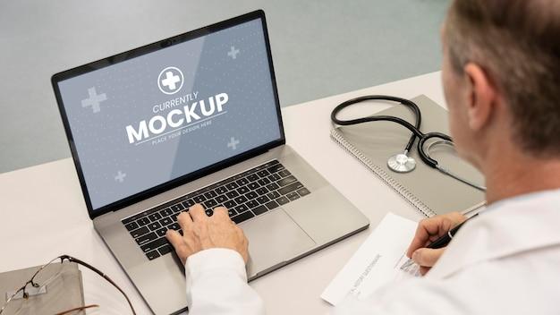 Zbliżenie lekarza piszącego na laptopie