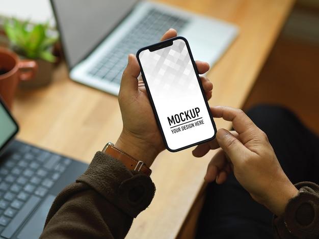 Zbliżenie męskiej dłoni za pomocą makiety smartfona siedząc w miejscu pracy