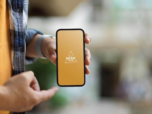 Zbliżenie męskiej ręki trzymającej makietę smartfona