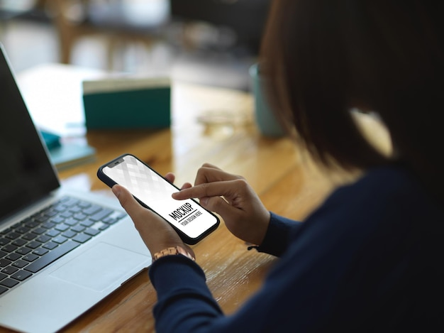 Zbliżenie na kobiece dłonie za pomocą makiety smartfona