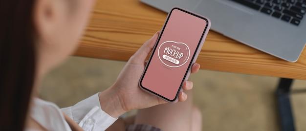 Zbliżenie na kobietę patrząc na makieta smartfona siedząc w miejscu pracy