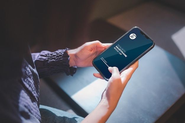 Zbliżenie na kobietę za pomocą smartfona w kawiarni