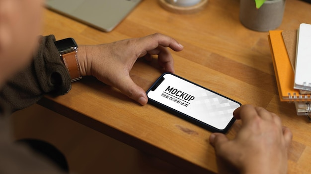 Zbliżenie na męskie dłonie za pomocą makiety smartfona na drewnianym stole