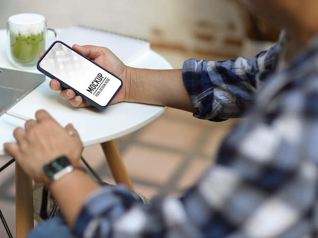 Zbliżenie na męskie dłonie za pomocą smartfona siedząc w biurze