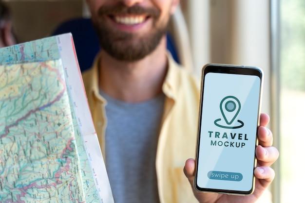 Zbliżenie na podróżującego młodego mężczyznę trzymającego makieta smartfona