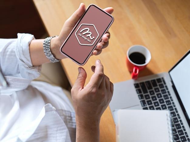 Zbliżenie na pracownika za pomocą makiety telefonu do badań