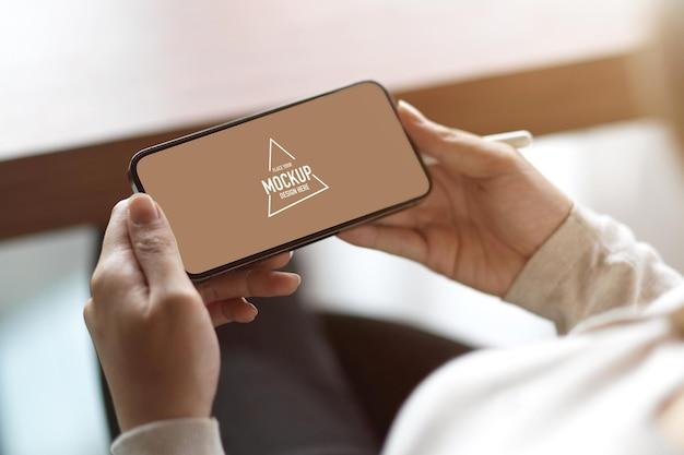 Zbliżenie na pusty poziomy ekran smartfona, kobieta trzymająca smartfon z pustą kopią miejsca