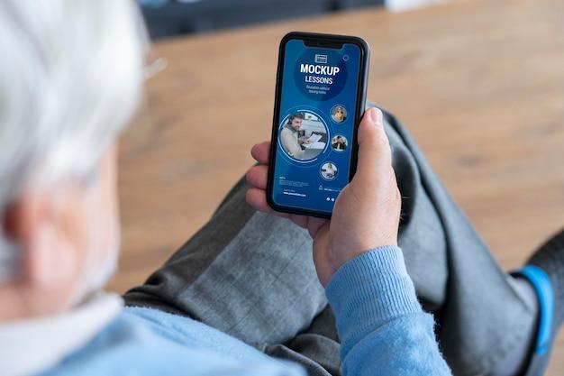 Zbliżenie na starszą osobę za pomocą makiety urządzenia cyfrowego