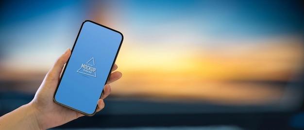 Zbliżenie ręki trzymającej smartfon i pokazujący ekran makiety
