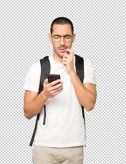 Zdezorientowany student korzystający z telefonu komórkowego