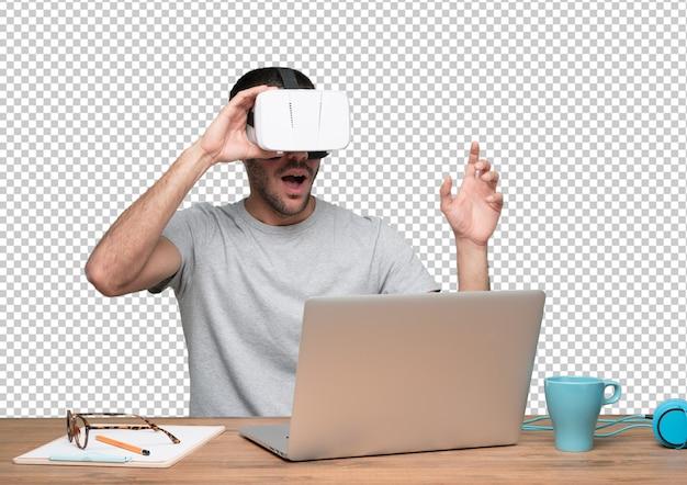 Zdumiony młody człowiek siedzi przy biurku i za pomocą okularów wirtualnej rzeczywistości