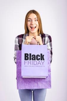 Zdziwiona kobieta trzyma purpurową torbę