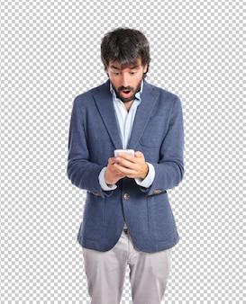 Zdziwiony mężczyzna opowiada mobilny nadmierny biały tło