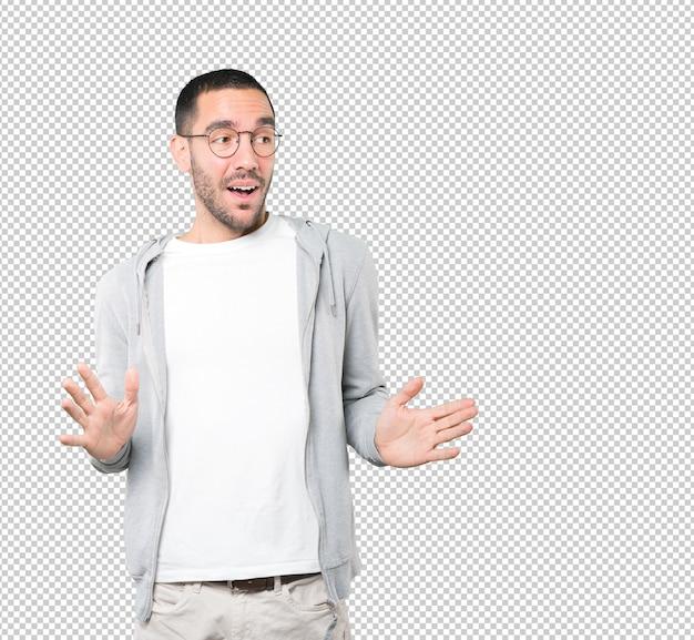 Zdziwiony młody człowiek patrząc gest