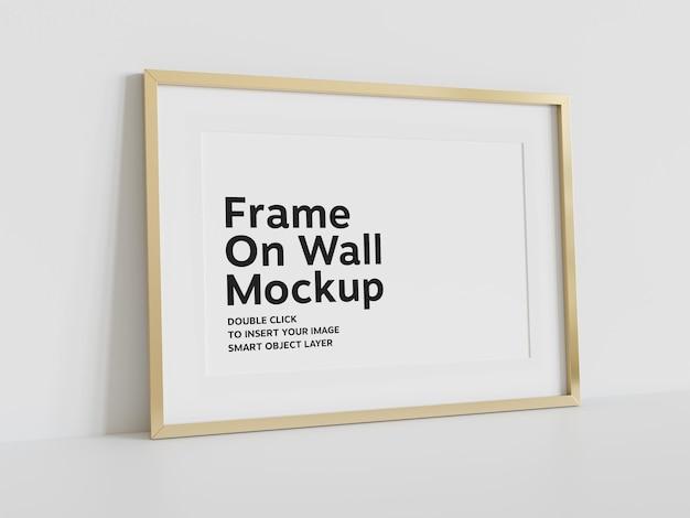 Złota rama oparta na ścianie makieta