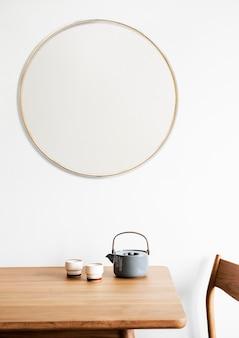 Złota ramka na białej ścianie przy zestawie do herbaty