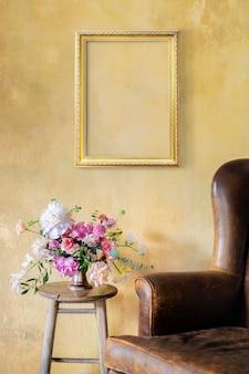 Złota ramka na żółtej ścianie przez kwiaty