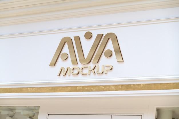 Złote logo na witrynie sklepu na ulicy makieta