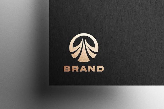 Złote tłoczone logo na czarnym papierze