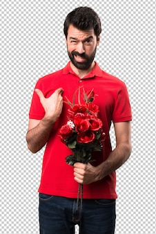 Zmęczony przystojny mężczyzna trzyma kwiaty