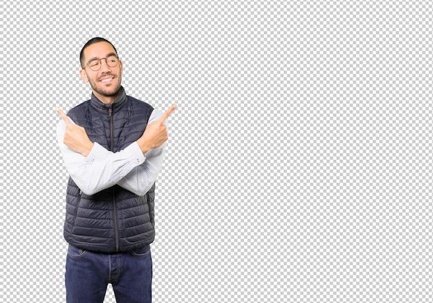 Zmieszany młody człowiek poiting w obu kierunkach