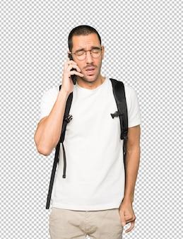 Znudzony student korzystający z telefonu komórkowego