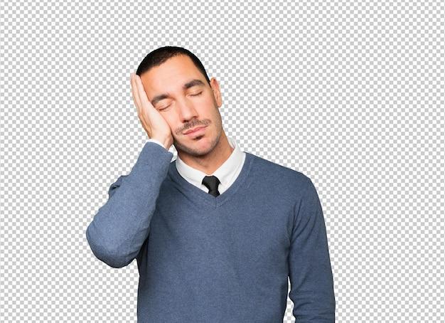 Zrelaksowany młody człowiek robi gest snu