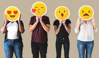 Zróżnicowani ludzie obleczeni w emotikony