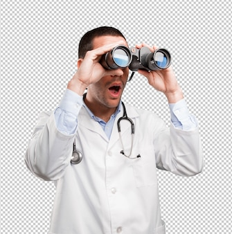 Zszokowany młody lekarz za pomocą lornetki