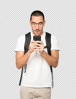 Zszokowany student korzystający z telefonu komórkowego