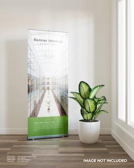 Zwiń makietę banera z rośliną przy oknie