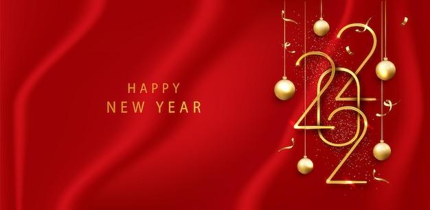2022 szczęśliwego nowego roku ze złotymi numerami na tle czerwonego sukna. wiszące złote metalowe cyfry 2022. nowy rok z życzeniami lub szablon transparentu.