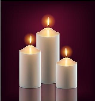 3 białe świece płonące w ciemności na białym tle