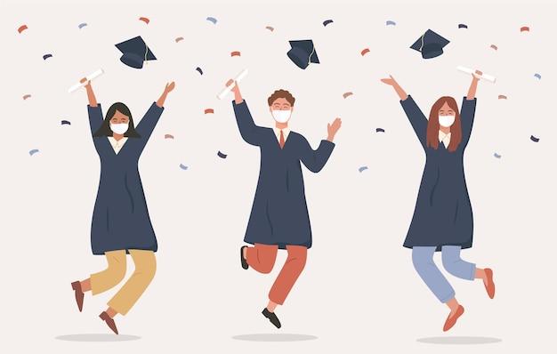 Absolwenci skaczący w akademickiej sukni