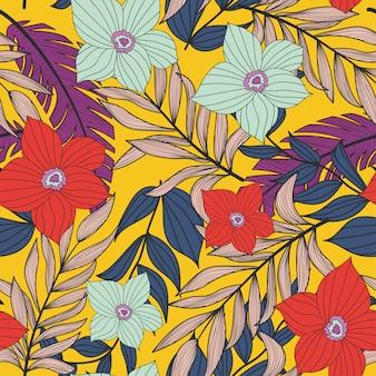 Abstrakcjonistyczny jaskrawy bezszwowy wzór z kolorowymi tropikalnymi liśćmi i roślinami na kolorze żółtym