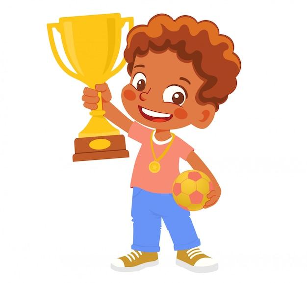 African american boy piłkarz zwycięzca. mały chłopiec trzyma złoty puchar